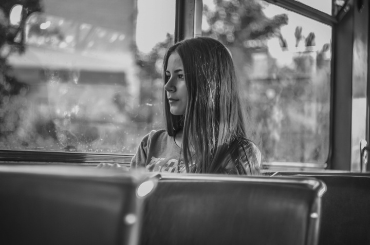 A young woman sitting by herself in a bus looking out the window.
