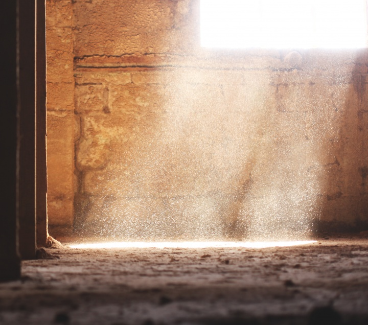 A an empty room with a brick walls and sunlight coming in from a window.