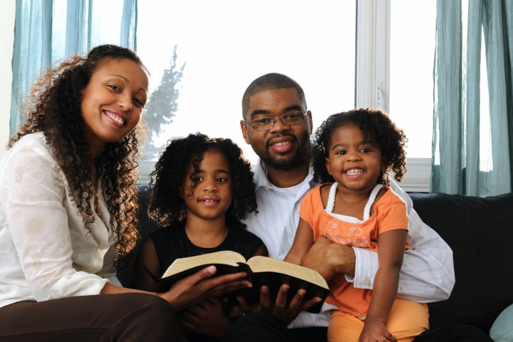 A young family reading Bible to children.