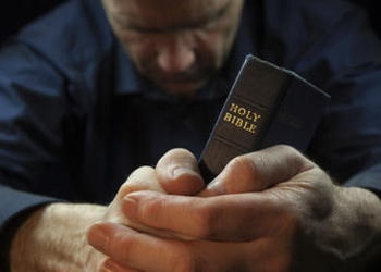 A man praying and holding the Holy Bible.