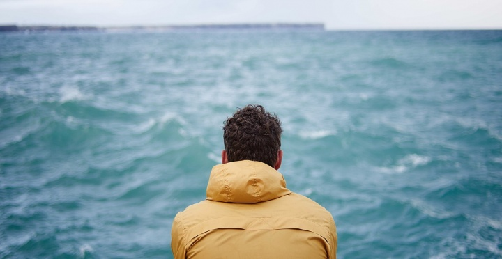A man watching the waves on a lake.