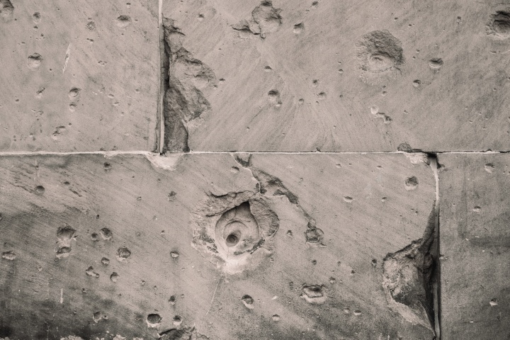 A concrete wall with cracks and holes.