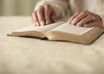 Older hands on top of a Bible.