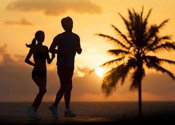Man and woman running on beach with a palm tree in the background.