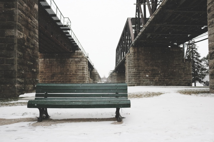 A park bench surrounded by snow and underneath a bridge.
