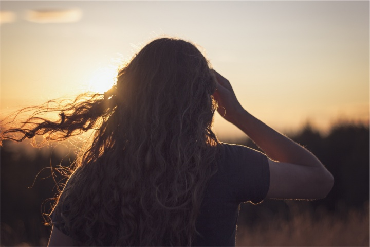 A young woman with her hair blowing in the wind.