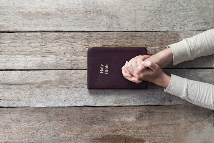 A person with their hands on top of a Bible that is on a table.