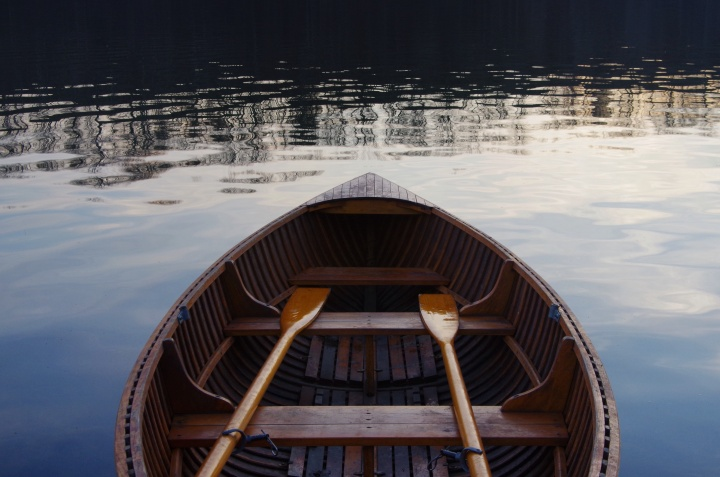 An empty wooden boat with two wooden oars.
