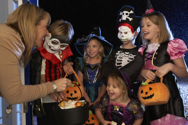 Little children dressed up in Halloween costumes trick or treating.
