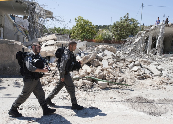 Two soldiers walking in street full of concrete rubble.