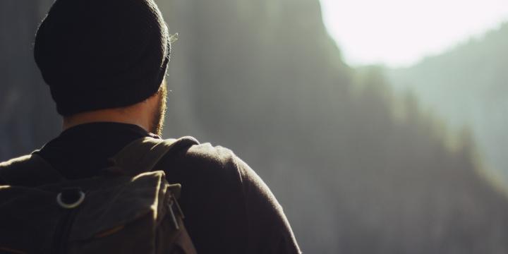 A young man looking over a mountain vista.
