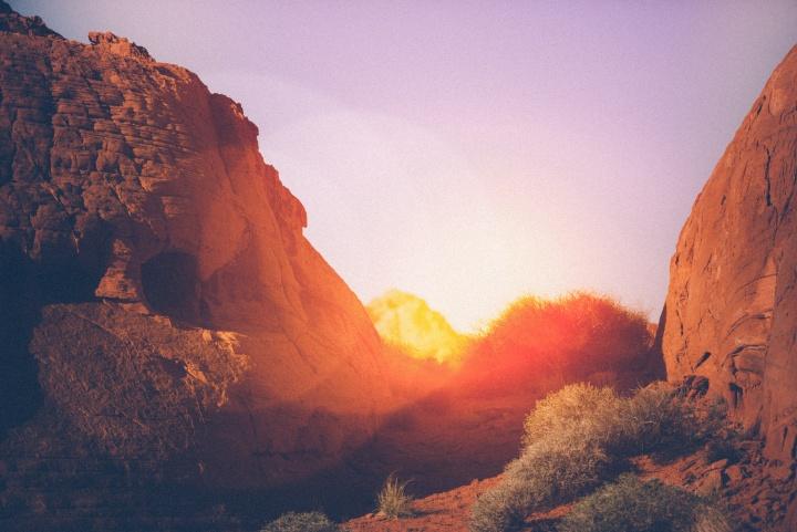 Sun setting behind rocks