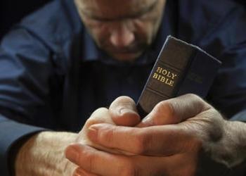 A man praying while holding a Bible.