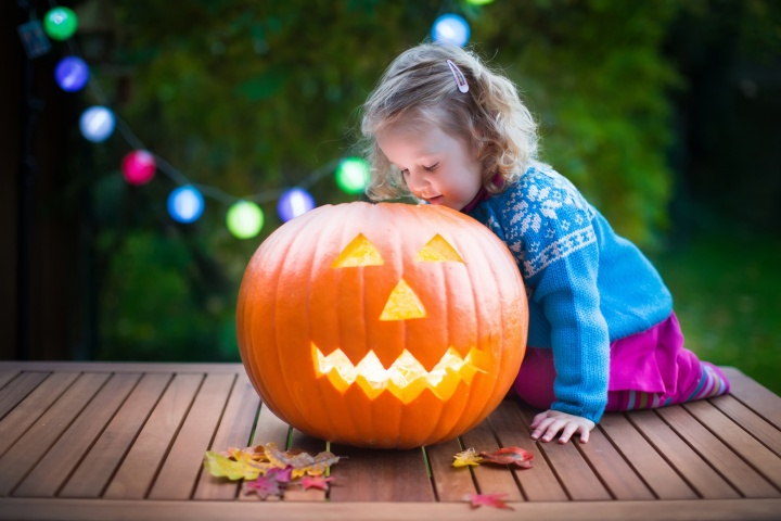 A little girl looking side a carved pumpkin jack o latern