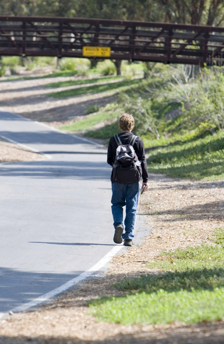 A young boy walking away wearing a backpack.