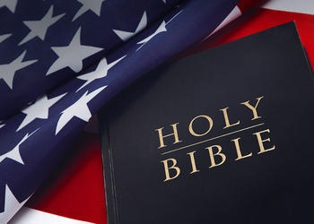Holy Bible on laying on top of United States flag