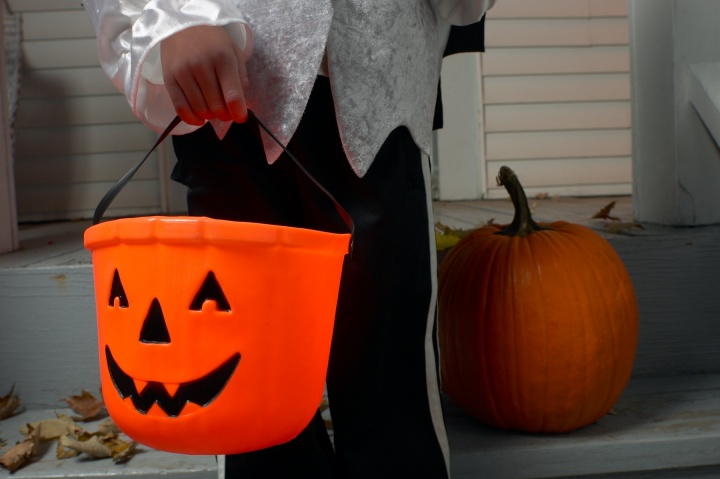 A child carry a jack-o-lantern bucket for candy.