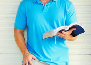 Man reading a Bible while leaning against a wall.
