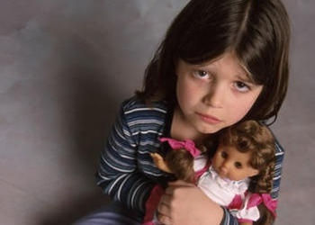 A small girl with a scared face holding a doll.