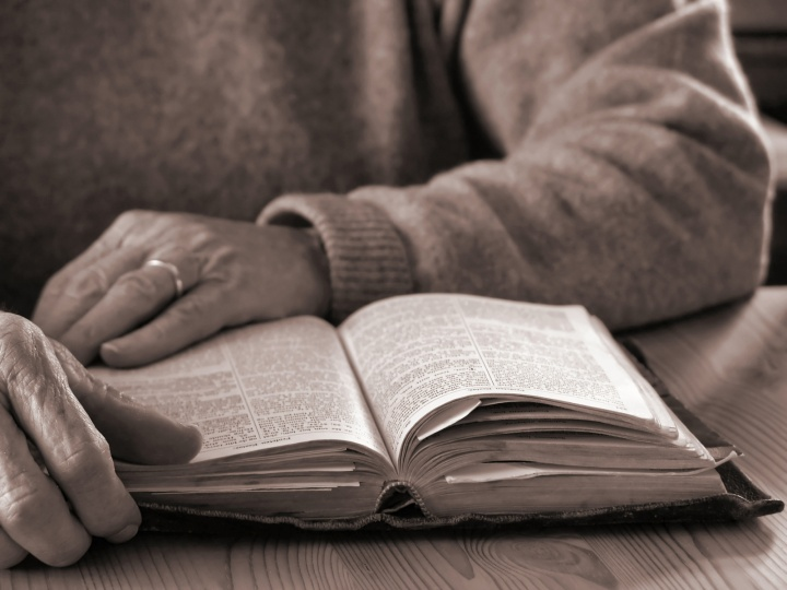 An older person reading a Bible.