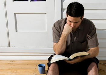 A man sitting and reading the Bible.
