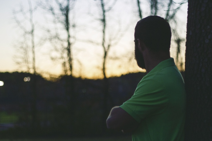 A man with arms crossed leaning against a tree looking at the sun setting.