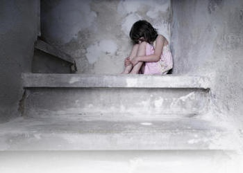 A little girl sitting on a concrete step.