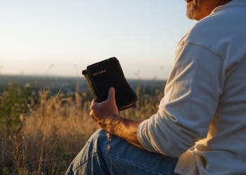 A man sitting on the ground holding an old Bible.