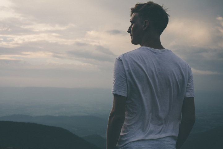 A young man looking over the vista of a mountain.
