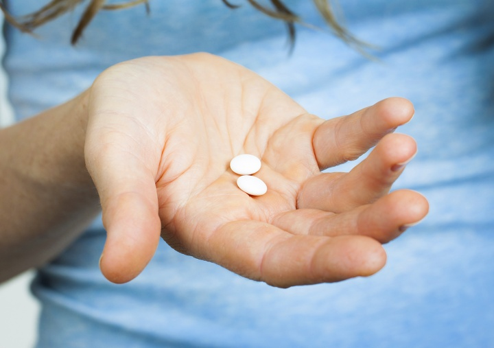 A woman holding pills in palm of hand.