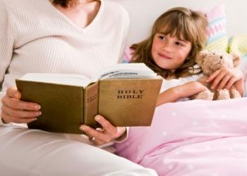 Mother reading Bible to child in bed - Teaching Youth Religious Values