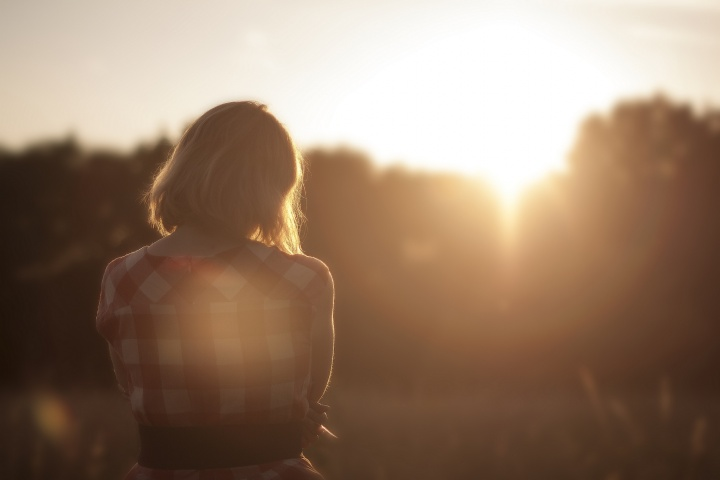 A girl sitting outside looking at sunset.