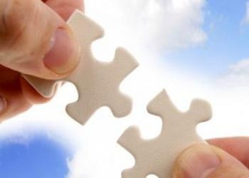 Hands Holding Jigsaw Puzzle Pieces In Front Of Blue Sky