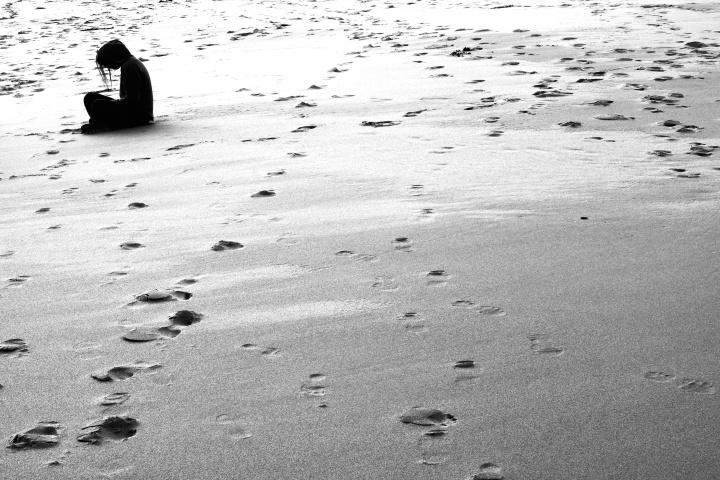 A woman sitting on deserted beach.