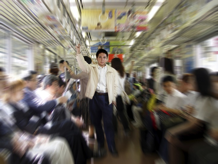 A man surrounded by people on a subway car.