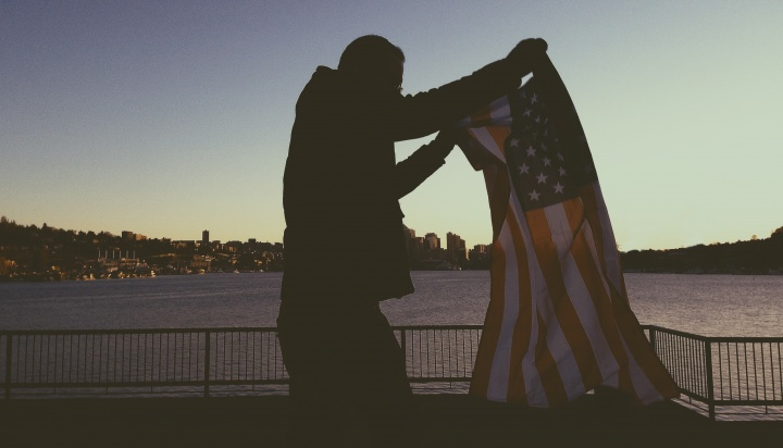 A man holding up the American flag.