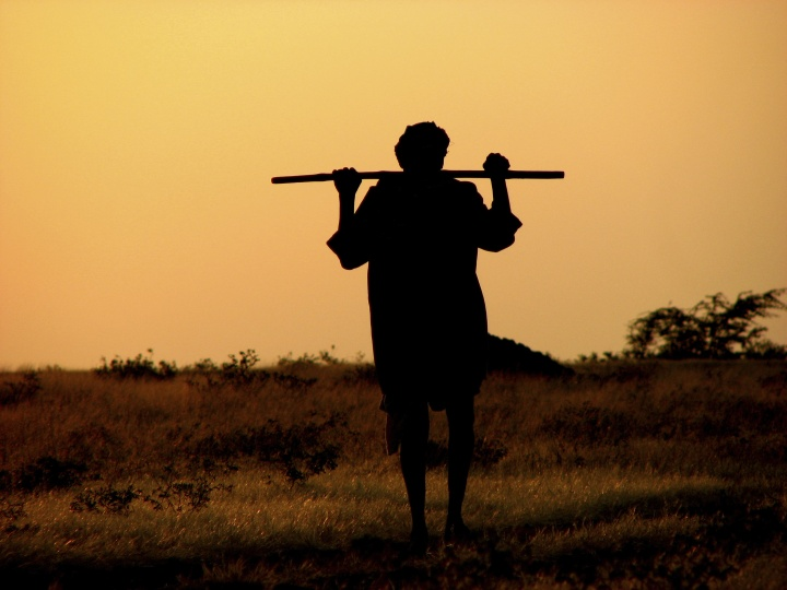 A shepherd carrying a rod.
