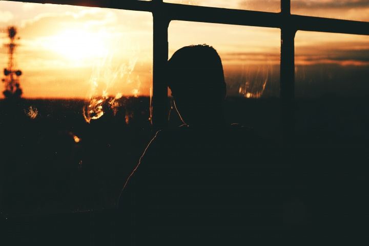 A young man looking out a window with the sun setting.