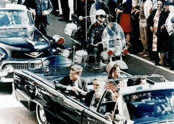 President John F. Kennedy  riding in a motorcade in Dallas, Texas.