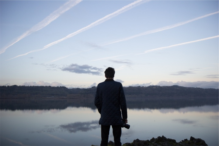 A man looking out over a lake.