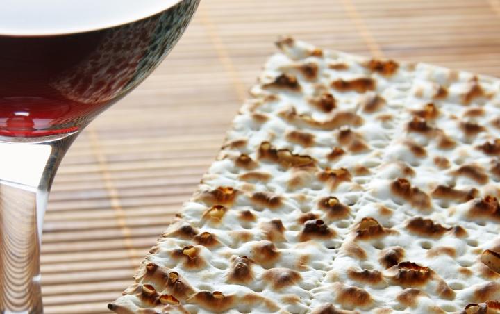 A glass of wine beside flat unleavened bread.