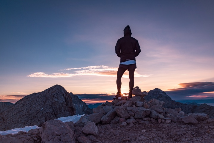 A person standing on top of a rocky hill watching the sunset.