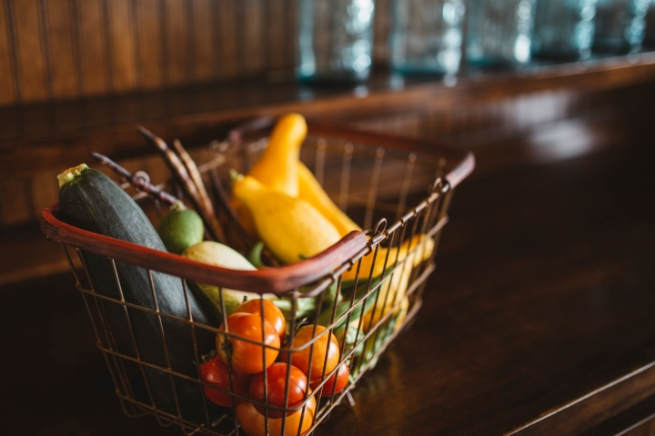 A wire shopping basket full of vegetables.