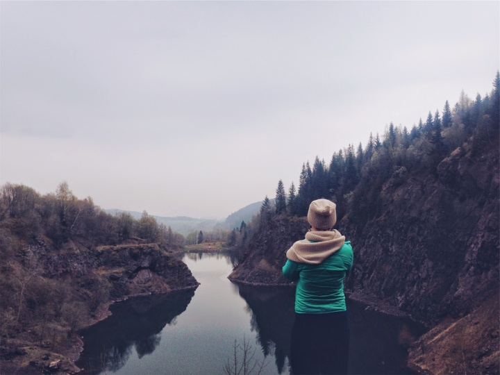 A young woman looking over a lake.