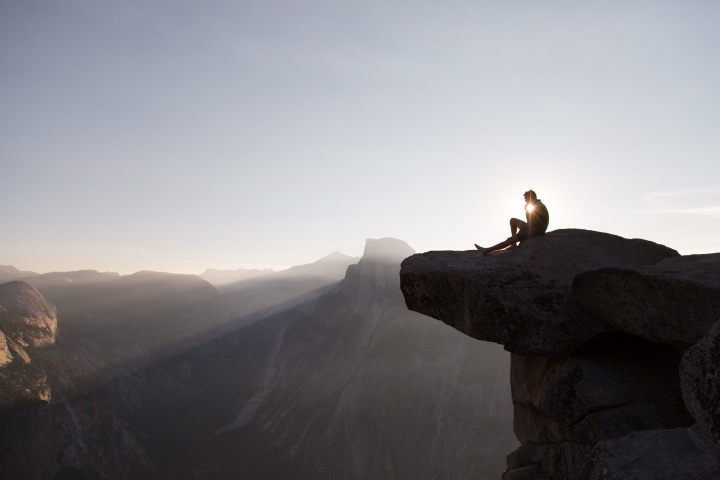 A man sitting on the edge of mountain cliff thinking.