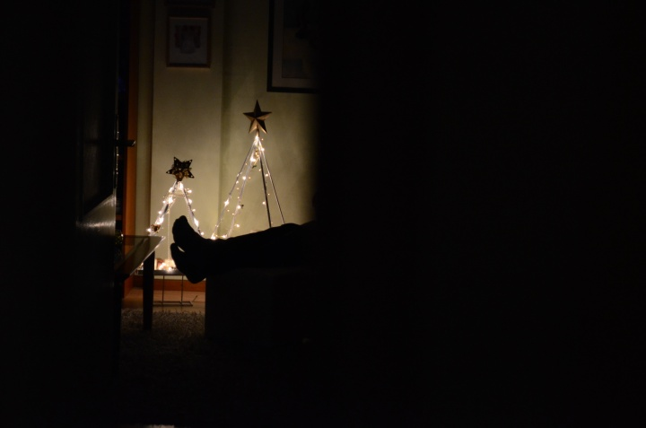 A person sitting in a dark room with Christmas lights.