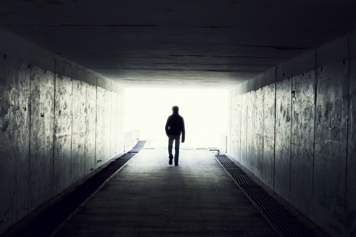 A man walking in a dark tunnel.