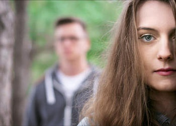 A young couple - woman in the foreground, man in the background blurred.