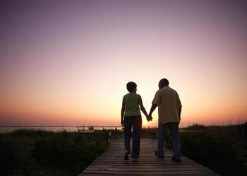 An older couple walking on a board walk while sun is setting.