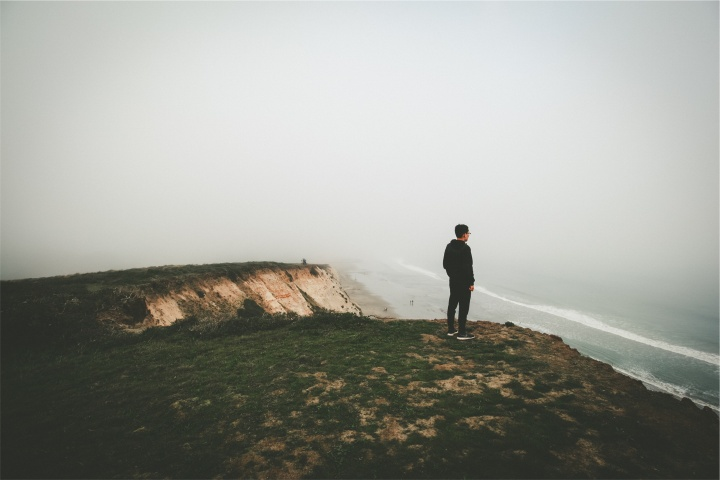 A man looking over a cliff toward the ocean.